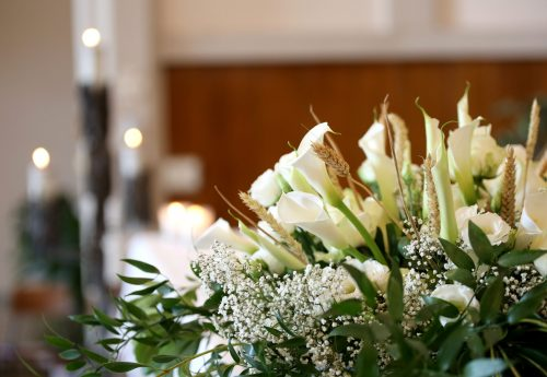 vase of flowers on an altar in the church and the candles on background